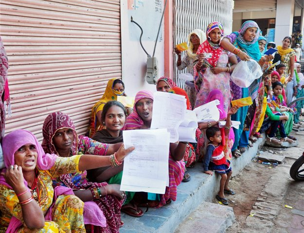 Women hold out the forms they had to fill as they wait outside a Bikaner bank in Rajasthan. Photo: PTI