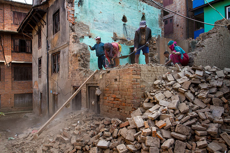 Workers continue the demolition of damaged home in Patan.