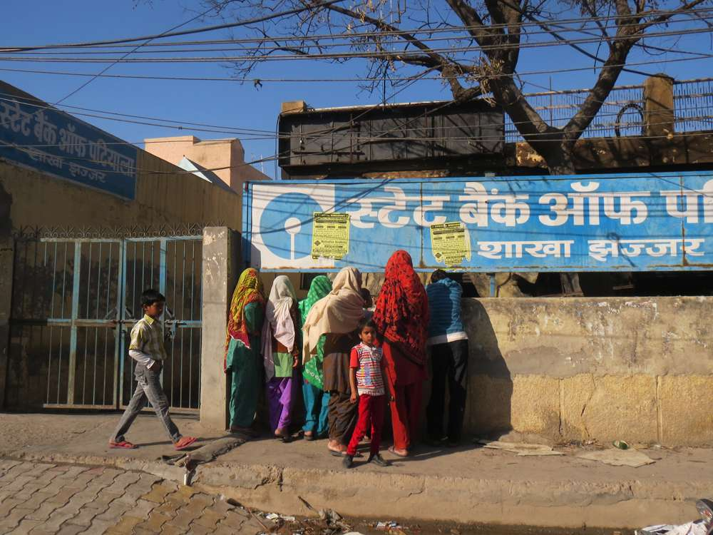 Visitors from a village gather outside the burnt State Bank of Patiala building in Jhajjar.