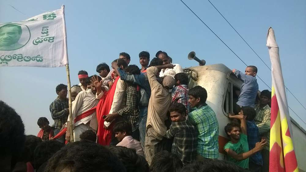 Protestors perch on the engine of the train before it is burnt. Photo credit: Y Jaswanth
