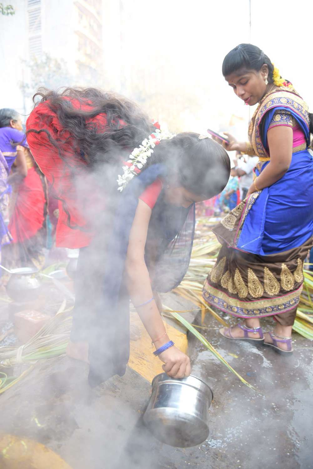 A woman drains out the excess water after cooking the rice.