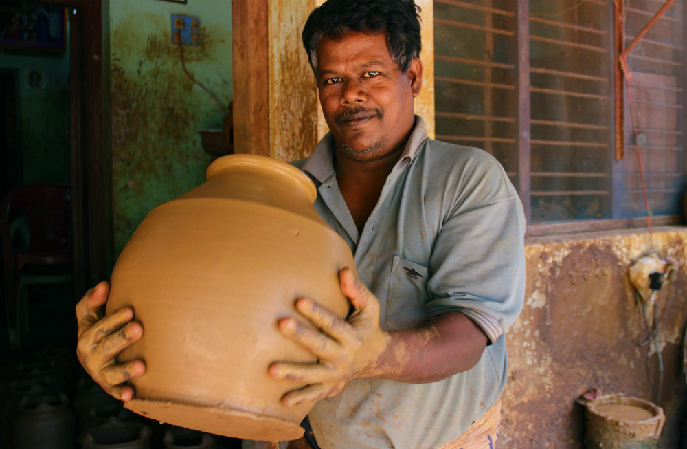 Ramesh lifts the raw clay plot from the wheel and carries it indoors.