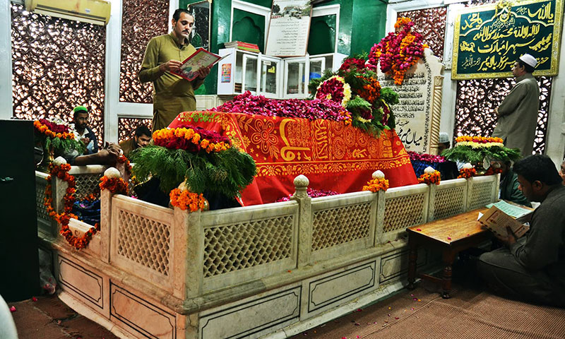 Mian Mir's grave is covered with flowers while people recite the Quran. Photo by Abdullah Khan.