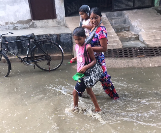 Villagers walk through water that has accumulated after about 10 minutes of rain. Photo: Menaka Rao