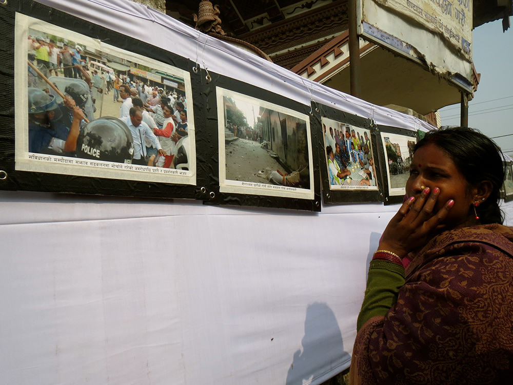 Eenar Jyoti from Chaukiaberia village in Parsa looks at photographs from the protests. Photo: Anumeha Yadav