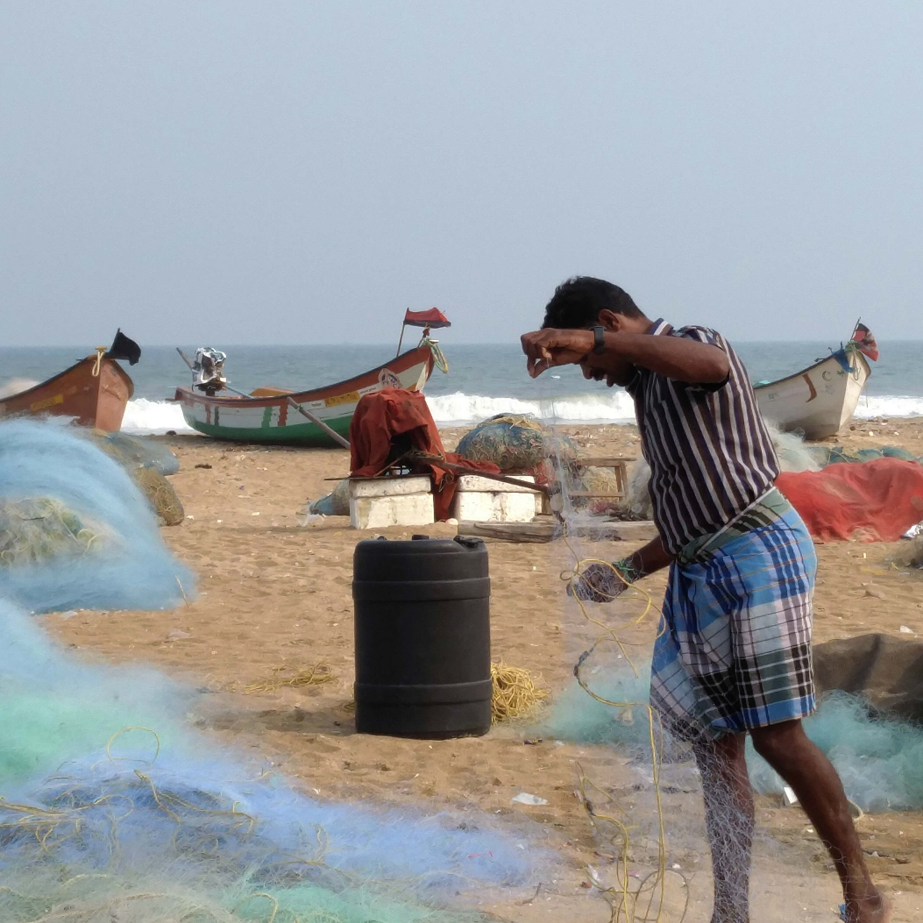 An artisanal fisherman folds his net on Marina beach in Chennai. (Photo credit: Vinita Govindarajan).
