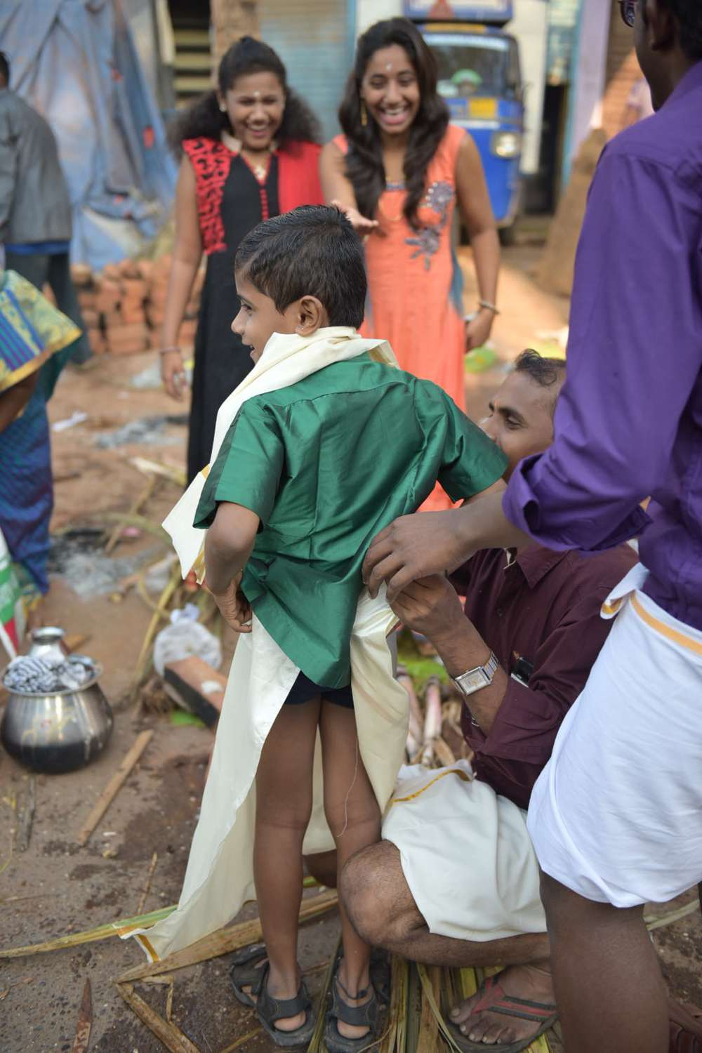 A boy struggles to keep his veshti on.