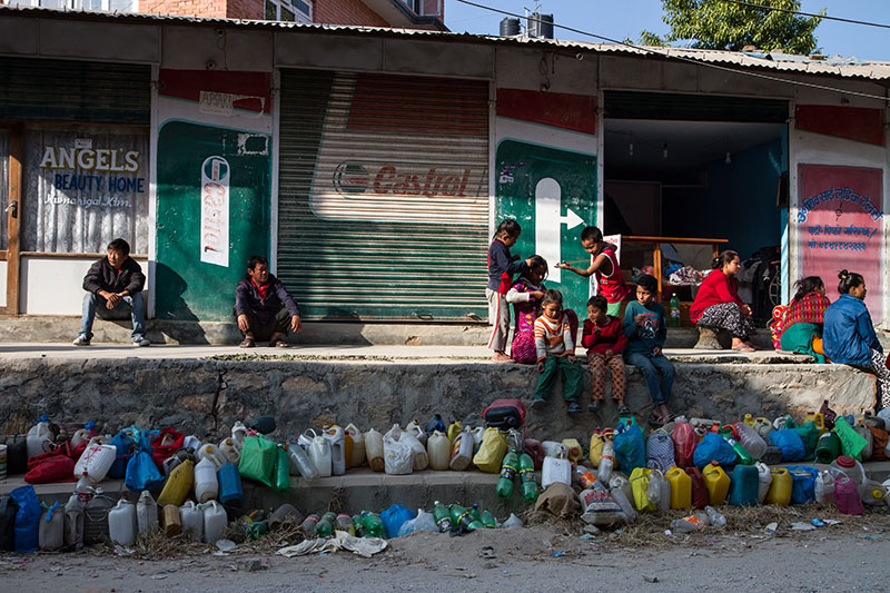 With plastic containers strung on a line, Kathmandu residents wait for the government to distribute kerosene.
