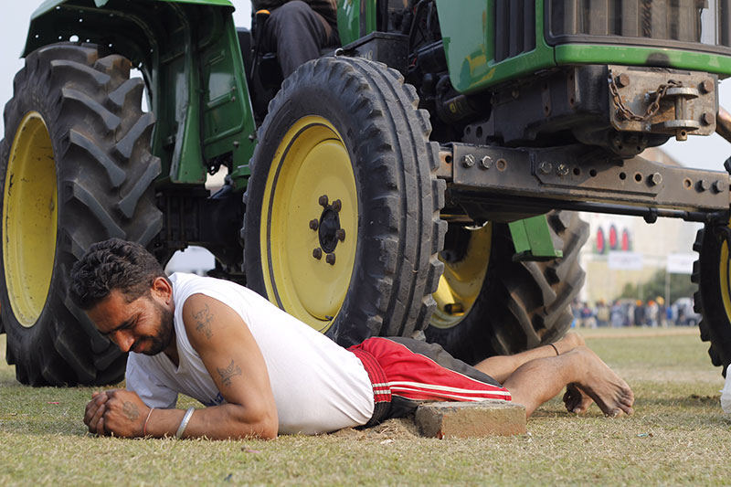 A man displays his toughness by letting a tractor run over him.