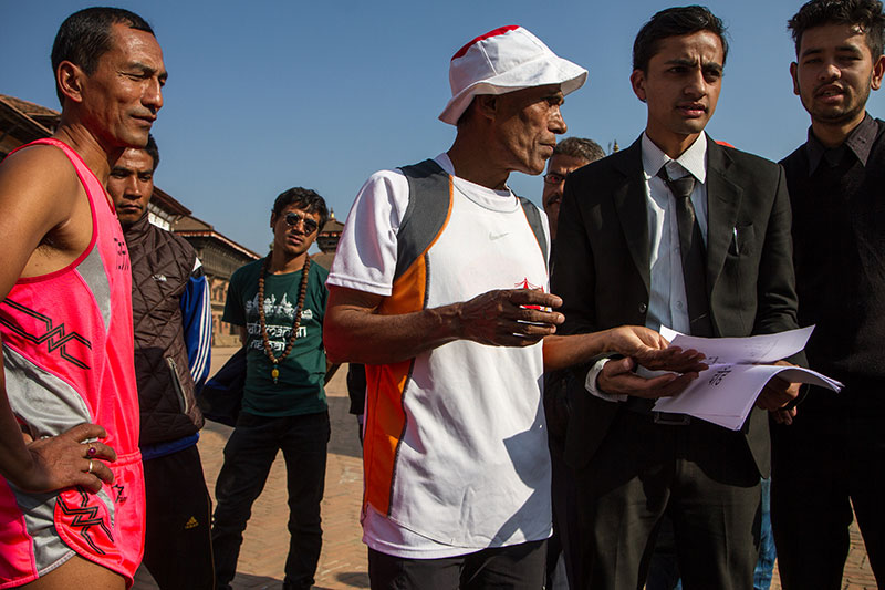 Baikuntha Manandhar (in white), a four-time Olympian and gold-medal winning athlete at the South Asian Games, prepares for the Marathon for Peace to raise awareness for women's and children's justice and to show that Nepal is safe for tourists. According to UNICEF, human traffickers targeted desperately poor families and forced them to give up their children after the earthquake. Manandhar and a small group of runners began among  the damaged temples at Bhaktapur Durbar Square and continued to Kathmandu and Patan.