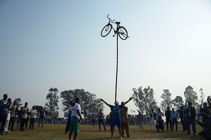 A competitor balances a bicycle on his mouth.