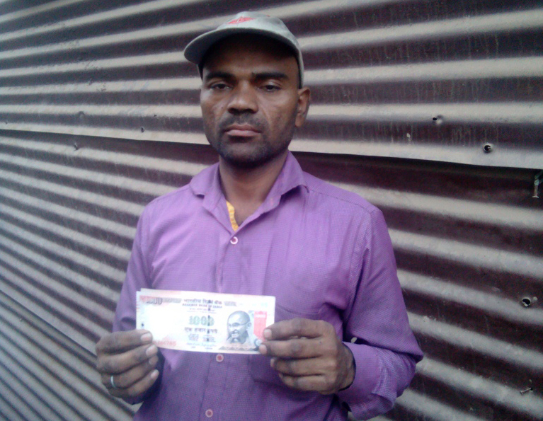 Loading-unloading worker Sanjay Kumar Yadav holds a Rs 1,000 note that he needs to get rid of.