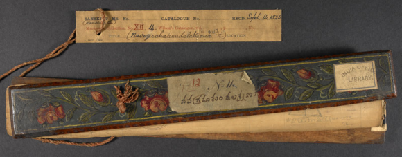 The outer 'patli' wooden boards of this manuscript are decorated with a blue and gold border, and with pink flowers and green leaves. A red silk cord runs through a hole in the palm leaves, which holds the manuscript together. When closed, the manuscript was secured by the cord, which was wrapped around the patli boards. The label recording the manuscript's despatch to London in 1825 is attached. (BL Mackensie XII.14 cover and label)