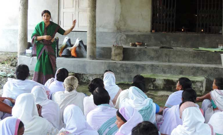 Purnima Barman speaks about Greater Adjutants to women at a village temple. The women have honored the bird that they now protect by adding it to sacred songs. Image Credit: Aaranyak