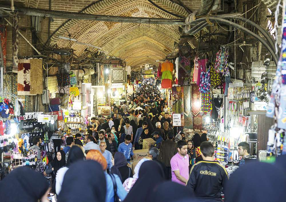 Crowds throng the Bazar Bozorg on a Thursday – the Iranian weekend. Traditionally, the Tehran bazaar was split into corridors, each specialising in different types of goods, including copper, carpets, paper, spices, and precious metals, as well as small traders selling all types of goods.