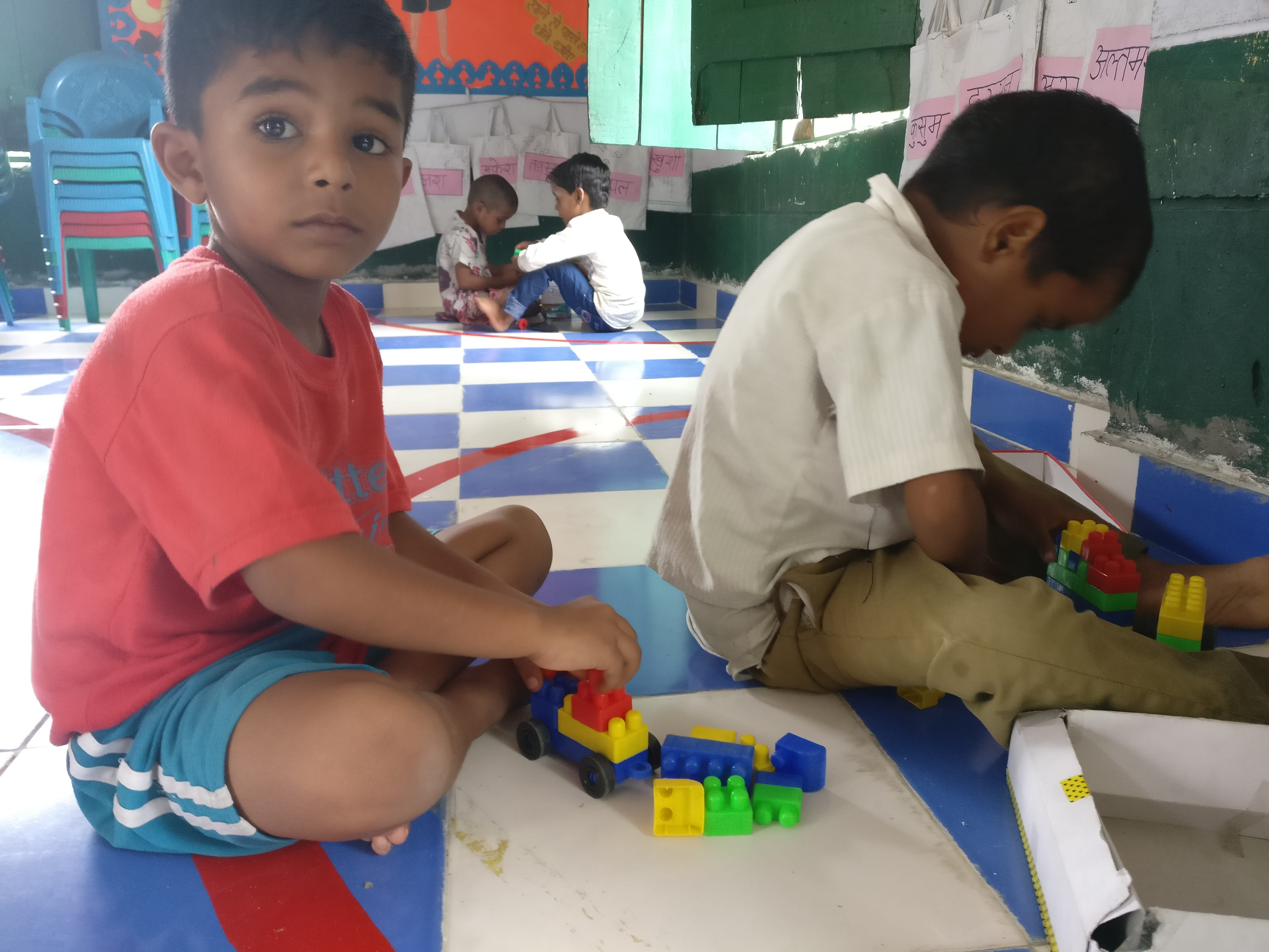 Altamas, 5, and his friend play with building blocks. Play areas are defined with tape. Bags with name tags hanging on the wall were made with the packaging the nutritional supplement came in. Photo credit: Shreya Roy Chowdhury