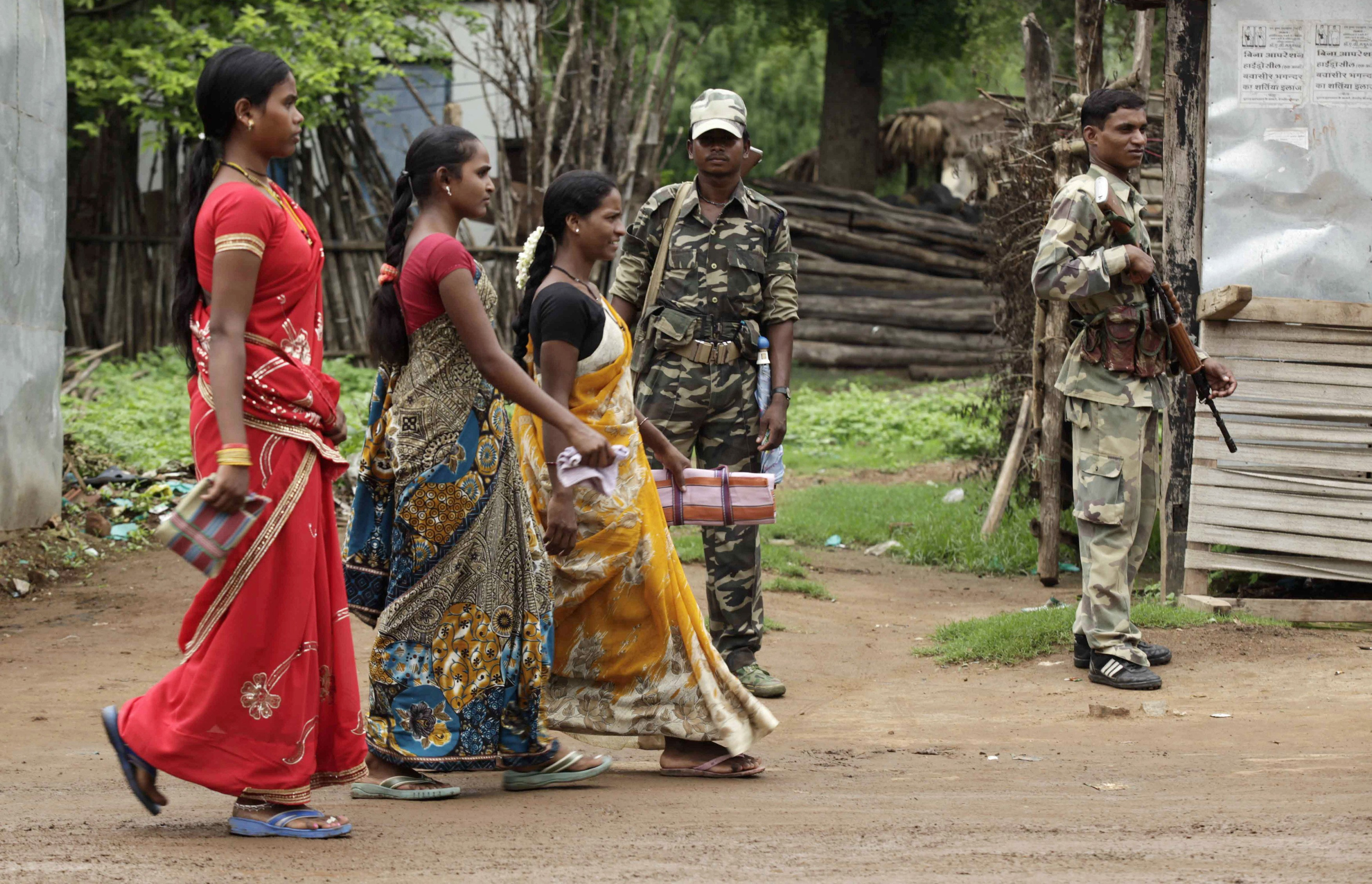Women in Awapalli village walk past members of the security forces. Credit: Rupak De Chowdhuri/Reuters.