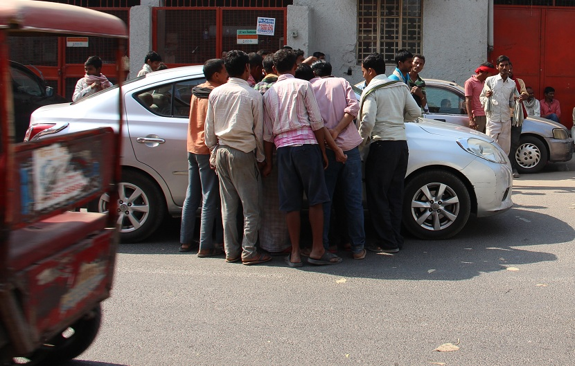 Workers surround the car of a potential employer in the hope of finding work. Photo: Aabid Shafi.