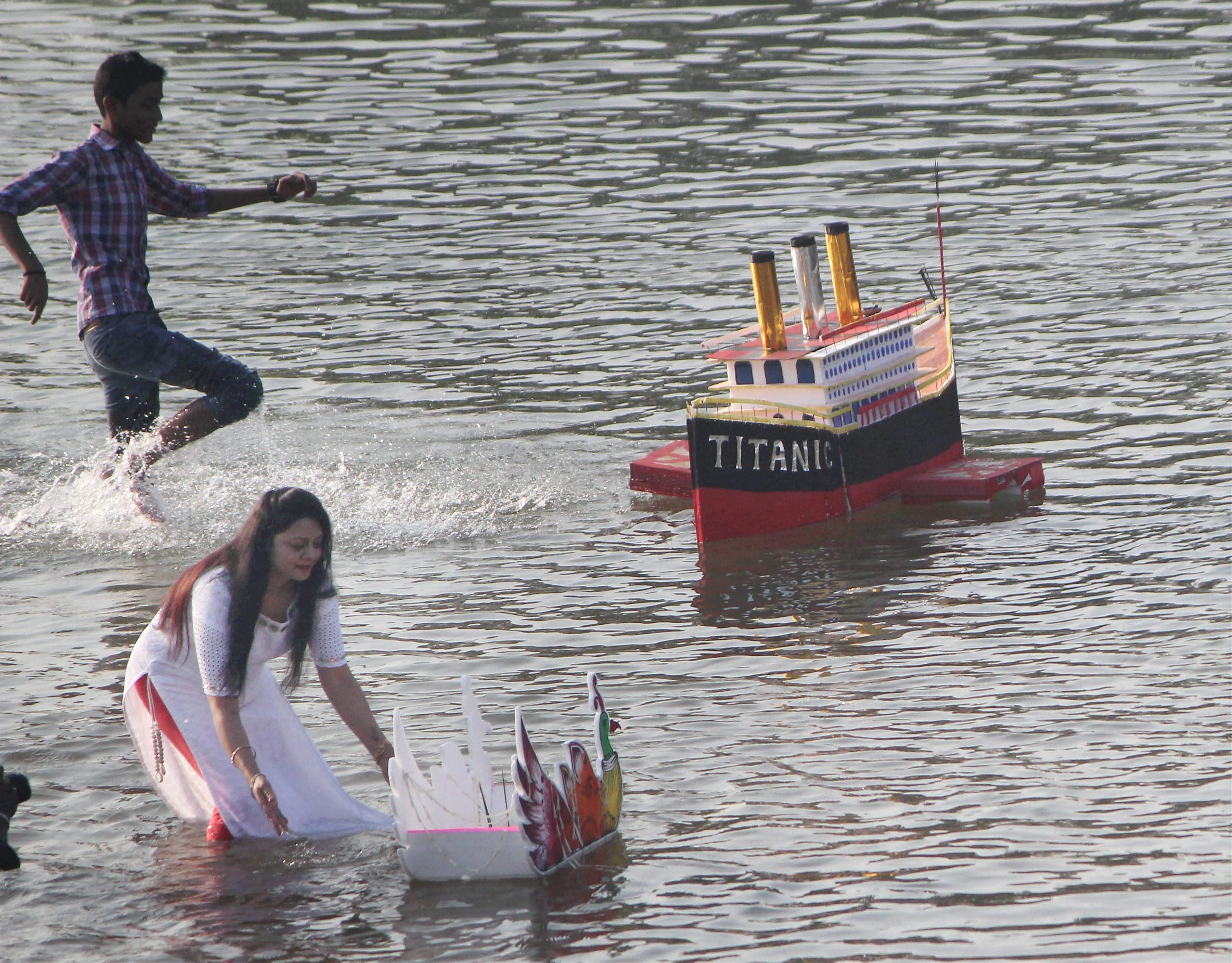 A woman gives her decorative boat a push in Daya river in Bhubaneswar, as part of Karti Purnima celebrations. (Credit: PTI)