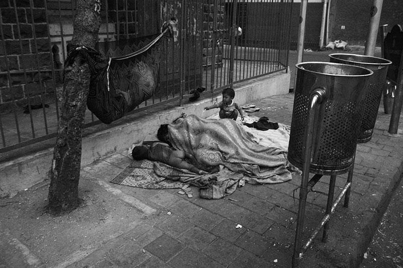 "A homeless family of five, including three infants, outside a college hostel near Chowpatty. The family has lived on the same pavement for more than a decade. They identify the space ""between the tree, dustbin and the signal"" as their home. In the last year, the college authorities barricaded part of the pavement."