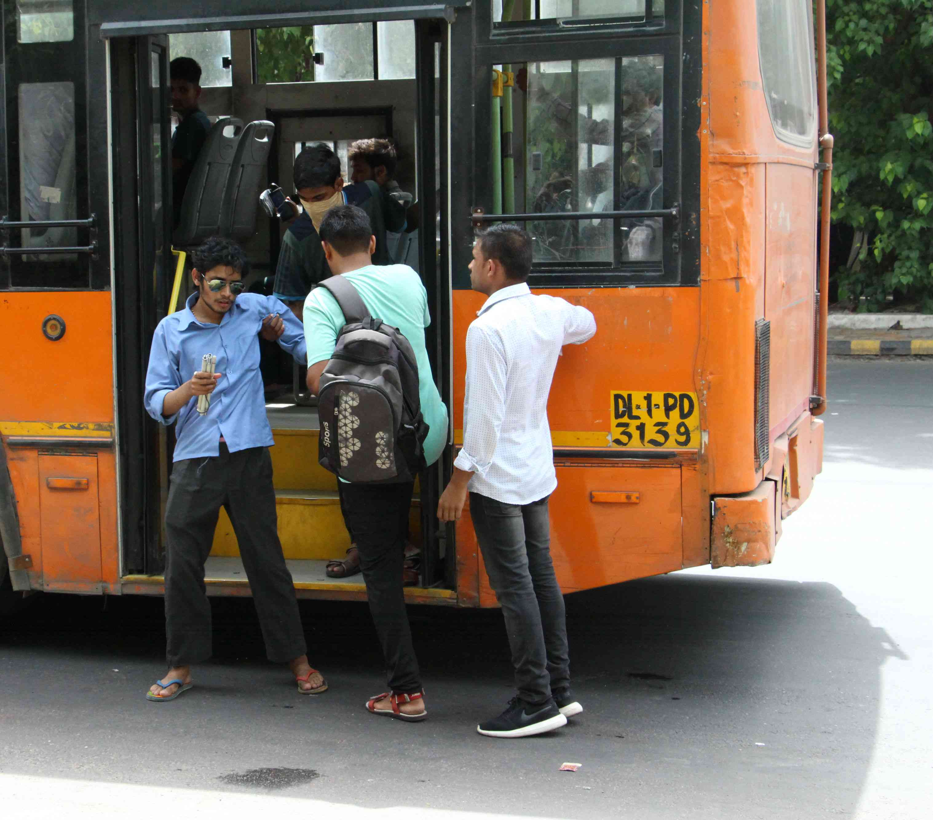 A man helps a visually impaired passenger to alight from a standard-floor bus in New Delhi.
