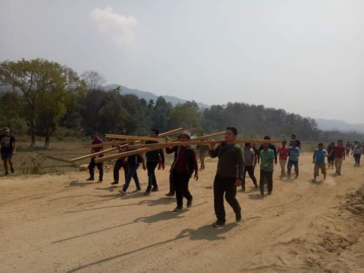 Mizo Zirlai Pawl activists with lumber to rebuild the shelter. (Photo credit: Special arrangement).