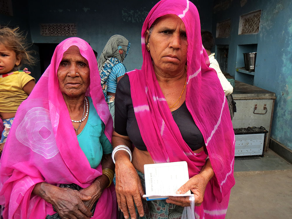 Geeta Devi (right) says she had to try to enrol in Aadhaar thrice, after her husband's name was misspelled two times. Dapu Devi (left) says she has not been able to access her pensions since it was shifted from the post-office to a bank four months back after she enrolled in Aadhaar.