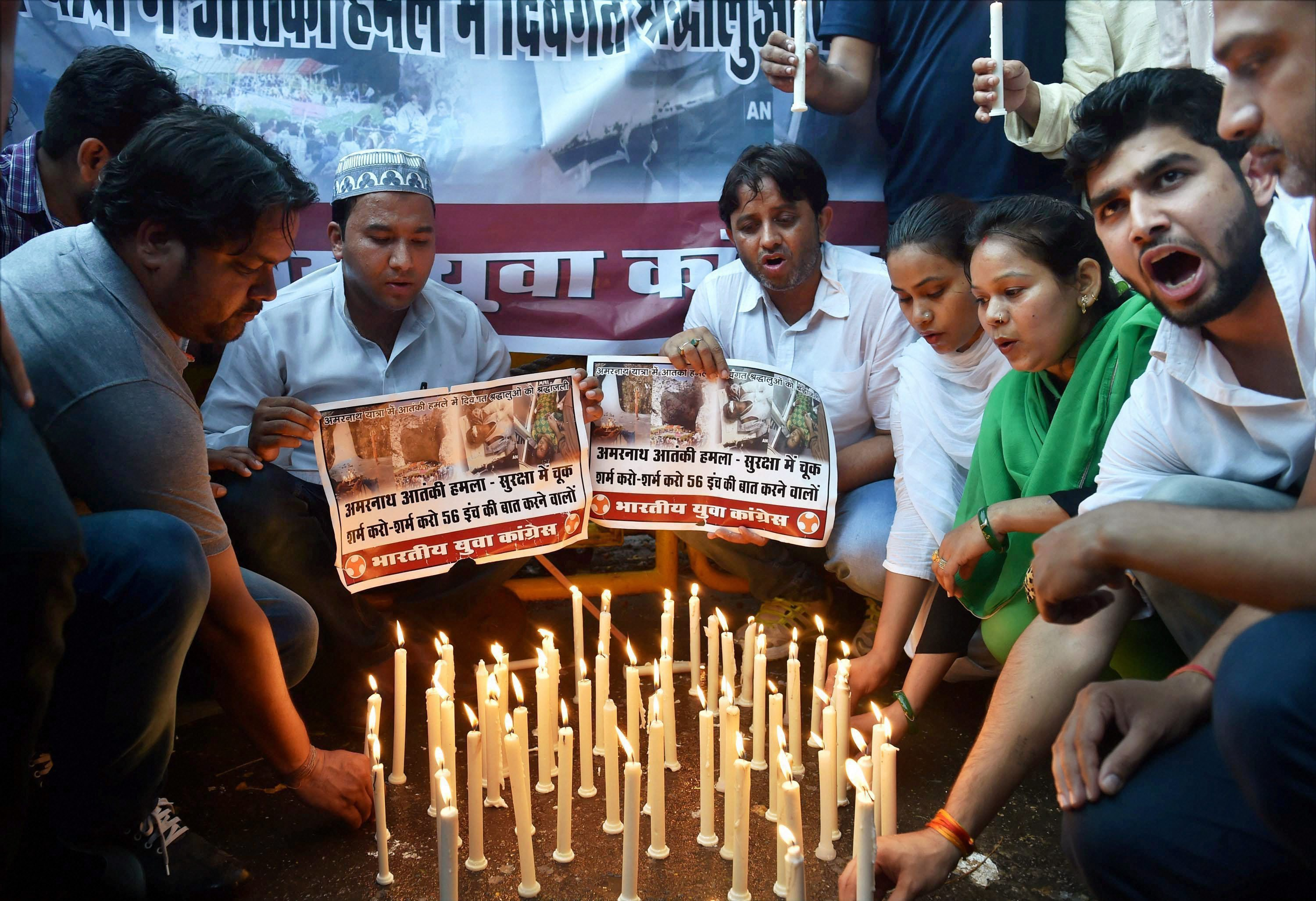 Youth Congress activists hold placards and light candles at a demonstration in New Delhi. (Pic: PTI)