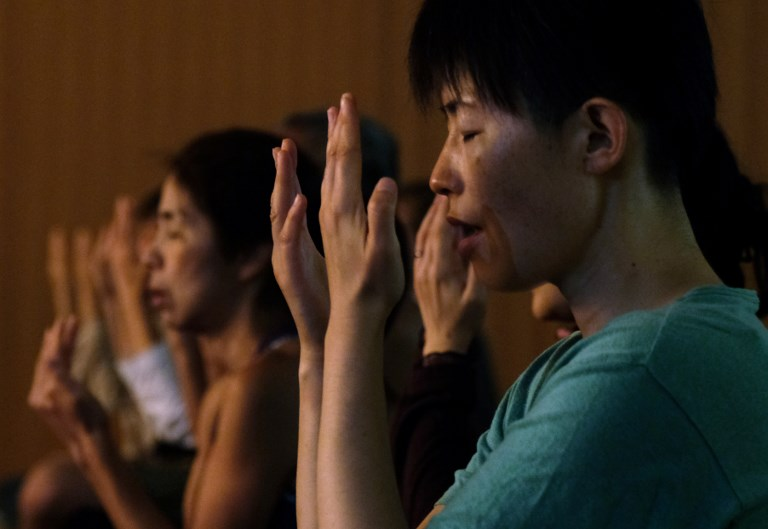 Yoga practitioners meditate during a special session on International Yoga Day at Tokyo's Zojoji Temple. (Kazuhiro Nogi/AFP)