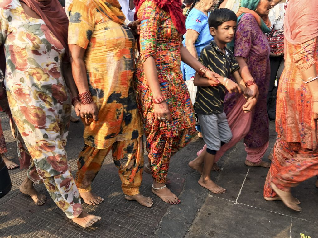 Women and children walk in a file, holding hands so that no one gets lost in the rush of activity at the ghats.
