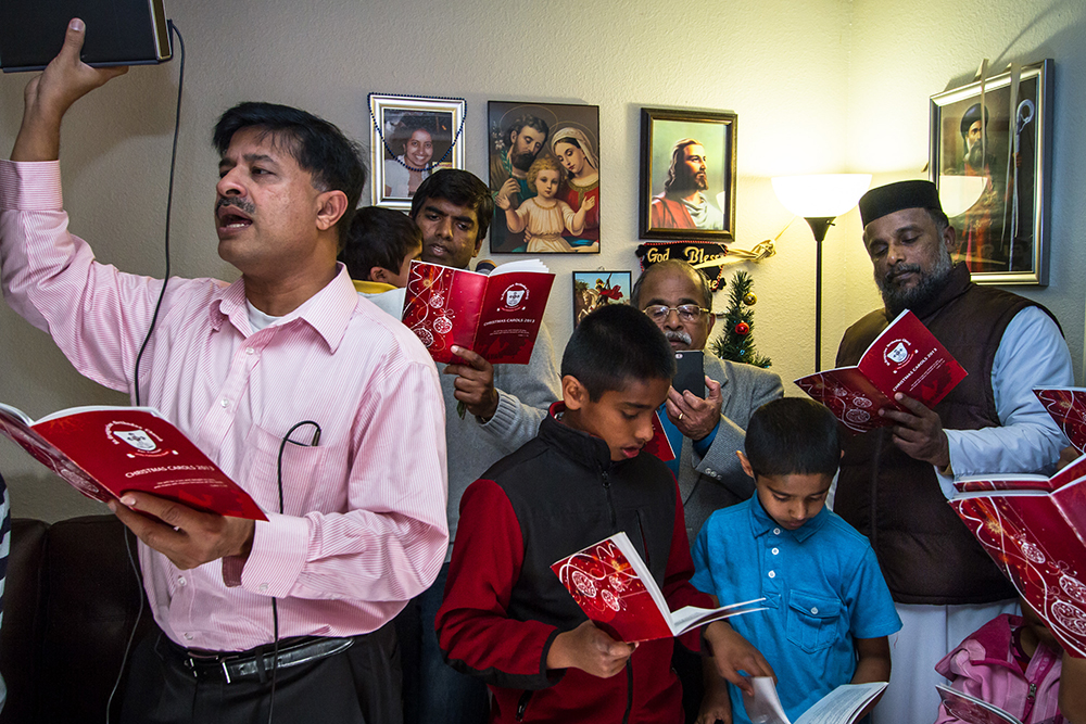 Union City, California: Eldo George leads the singing with a speaker attached to his phone, as members of St. Gregoriose Orthodox Church sing Christmas carols in a parishioner's home.