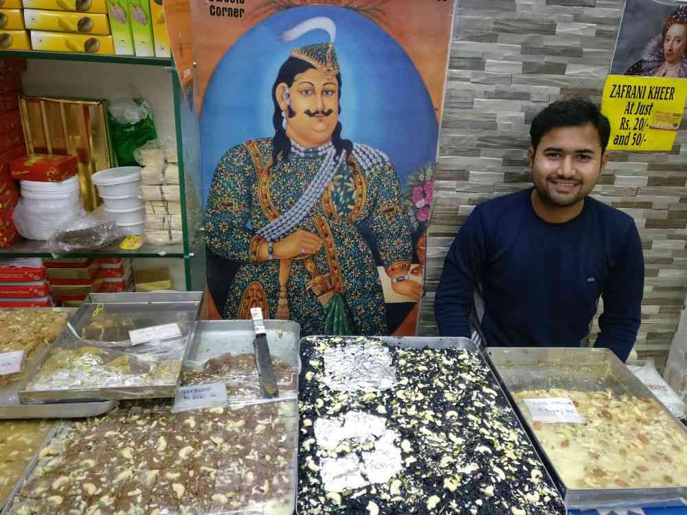 Amir Ali, the owner of Rahmat Ali, with trays of sweetmeats, including black gajar halwa. Photo credit: Shoaib Daniyal.