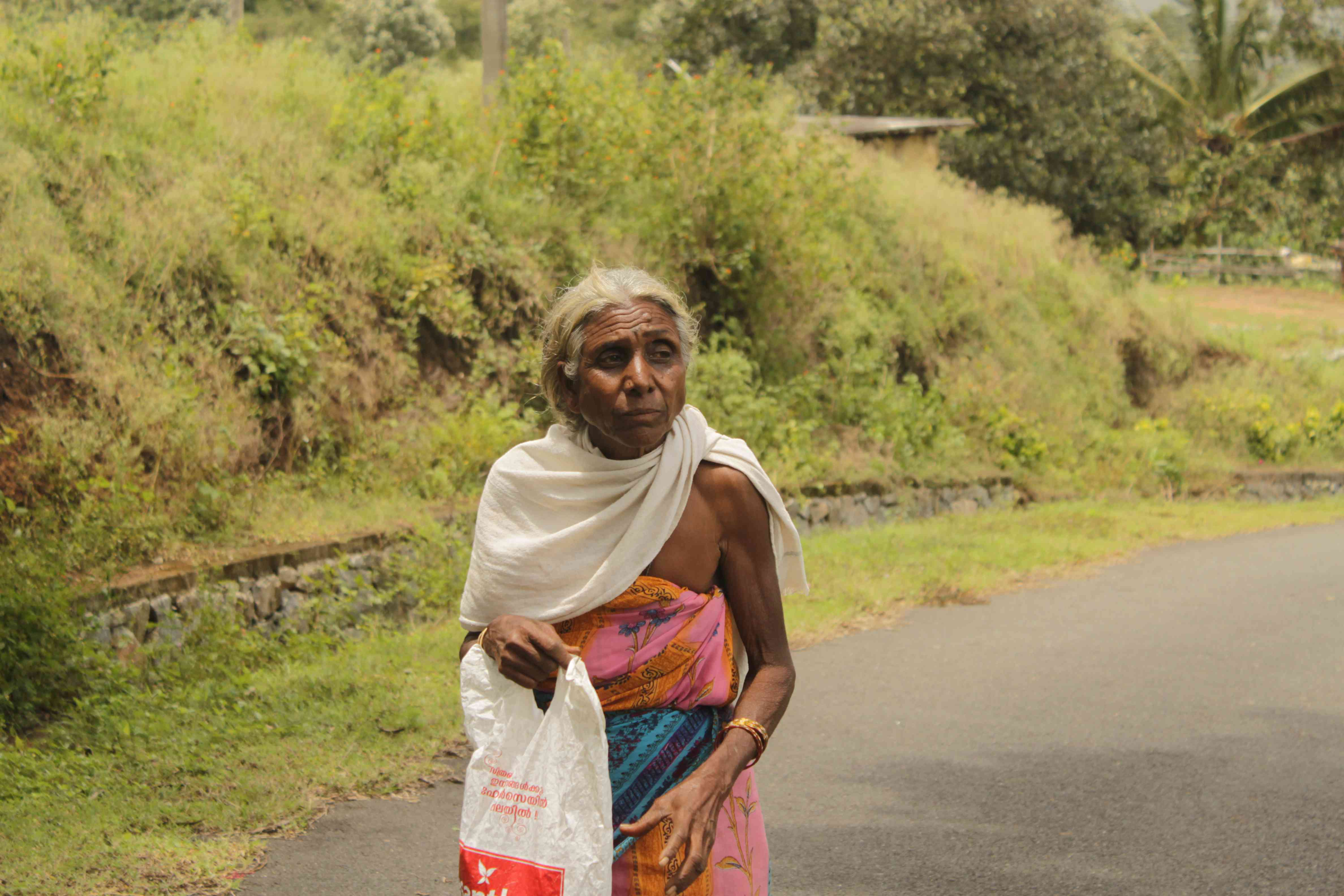 An Adivasi woman walks towards the Kottiarkandi relief camp. Photo credit: S Senthalir