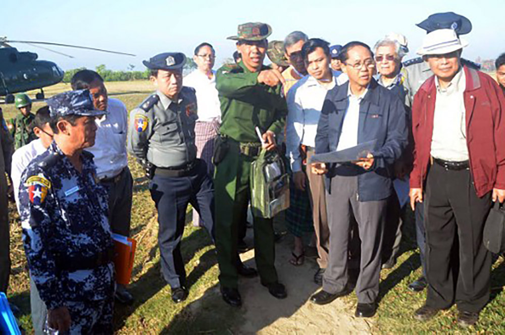 This handout photograph taken on December 12, 2016 and released on December 13, 2016 by the Myanmar State Counsellor Office shows a military official, centre, briefing Myanmar Vice President Myint Swe (2nd man on the right, in blue jacket), head of the Rakhine State Investigation Commission, during his visit to Gwazon, a Muslim majority village in Maungdaw located in Rakhine State near the Bangladesh border, where a military officer was killed by a group of attackers on November 12. Image Credits: AFP
