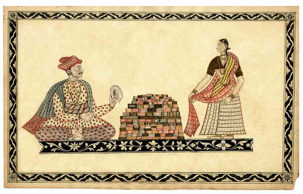 Traders in Chintz, Andhra (from the TAPI Collection). He sits cross-legged on the plinth wearing a yellow jama and pale lilac paijama with a blue shawl and a pale red turban with an interesting back. He holds out what is possibly his stock book towards a woman customer who stands at the other side of the central pile of patterned textiles. She wears a white skirt, brown bodice and two dupattas, one yellow tied close to her body and another pale red whose ends she holds out to the dealer as if seeking to match it or show its length. They are positioned on a black plinth decorated with floral designs while the frame shows a meander pattern.