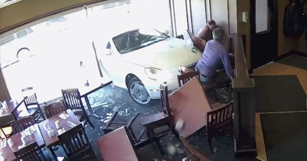Watch: Two men walk off after being hit by a car smashing through a restaurant wall