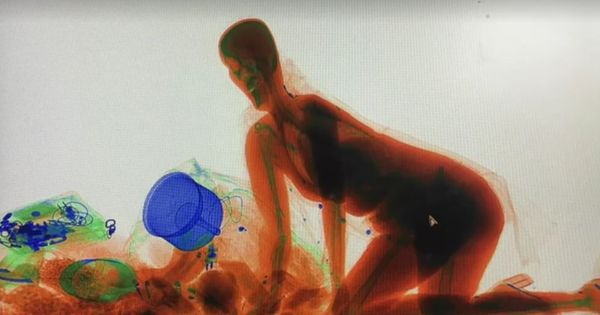 Caught on camera: Refusing to part with her bag, this woman climbed into an x-ray machine