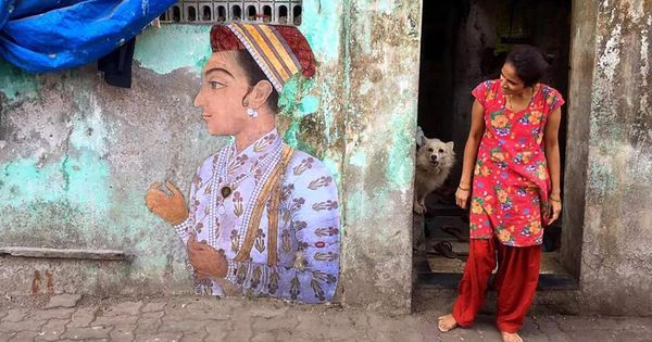 An artist is pasting images of paintings from museums on Indian street corners