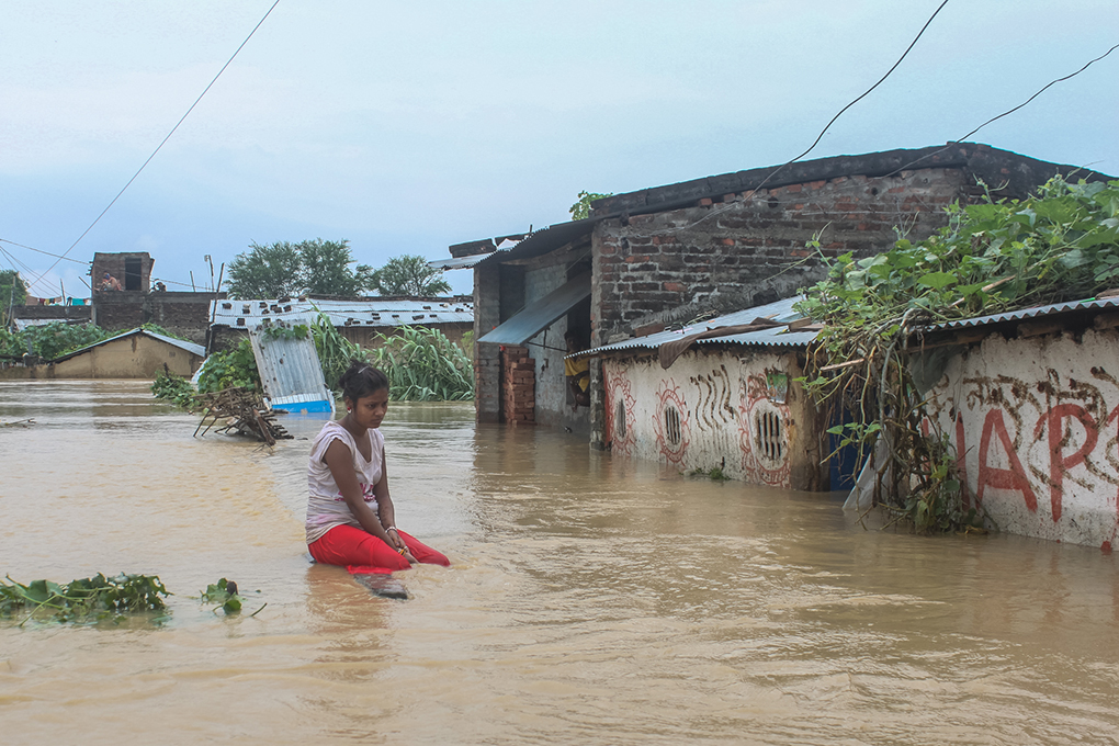 A woman contemplates her flooded home. Photo credit: Munna Saraff