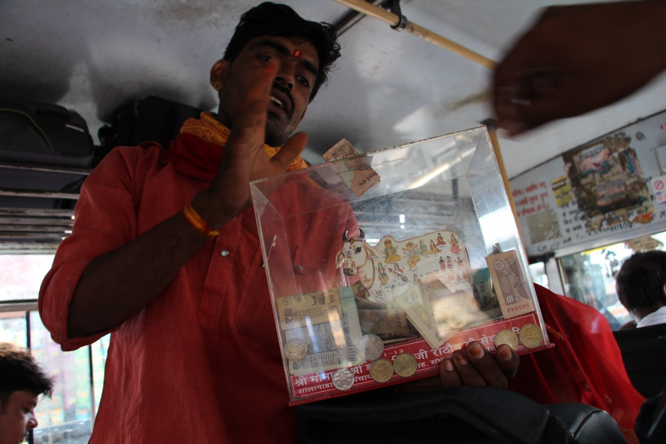 On a bus from Balotra to Barmer, a man raised donations for a cow shelter.