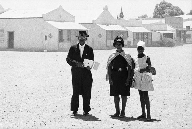 An elder of the Dutch Reformed Church walking home with his family after the Sunday service, Carnavon, Cape Province (Cape), January 1968. David Goldblatt