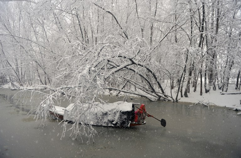 A Kashmiri woman rows her boat during heavy snowfall on Dal Lake in Srinagar on January 6. Credit: Tauseef Mustafa/AFP