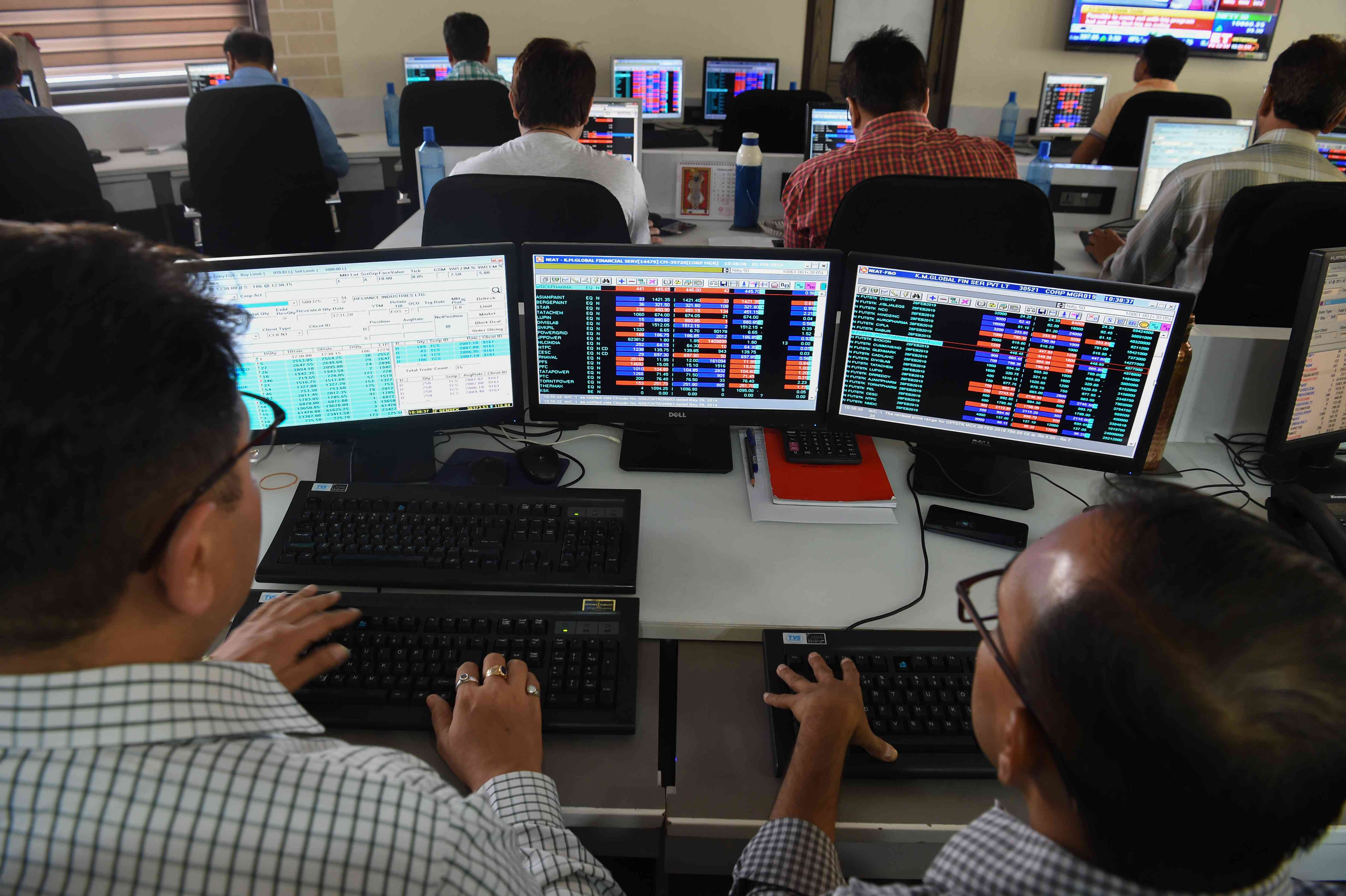 Stockbrokers keep a watch on share prices while trading at a brokerage house in Mumbai on February 1. (Credit: Indranil AFP)