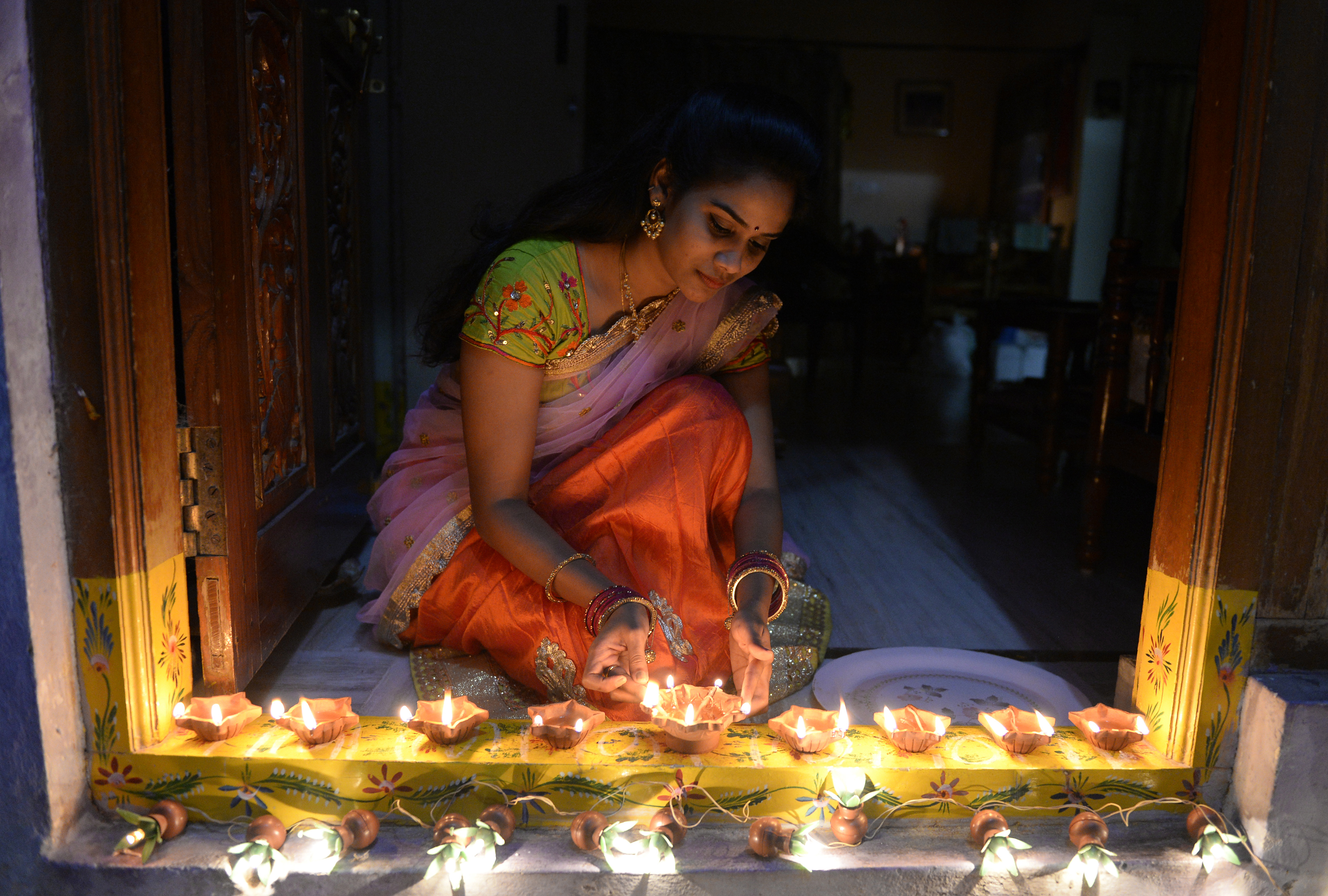 A woman places lamps at her home in Hyderabad. (Credit: AFP)