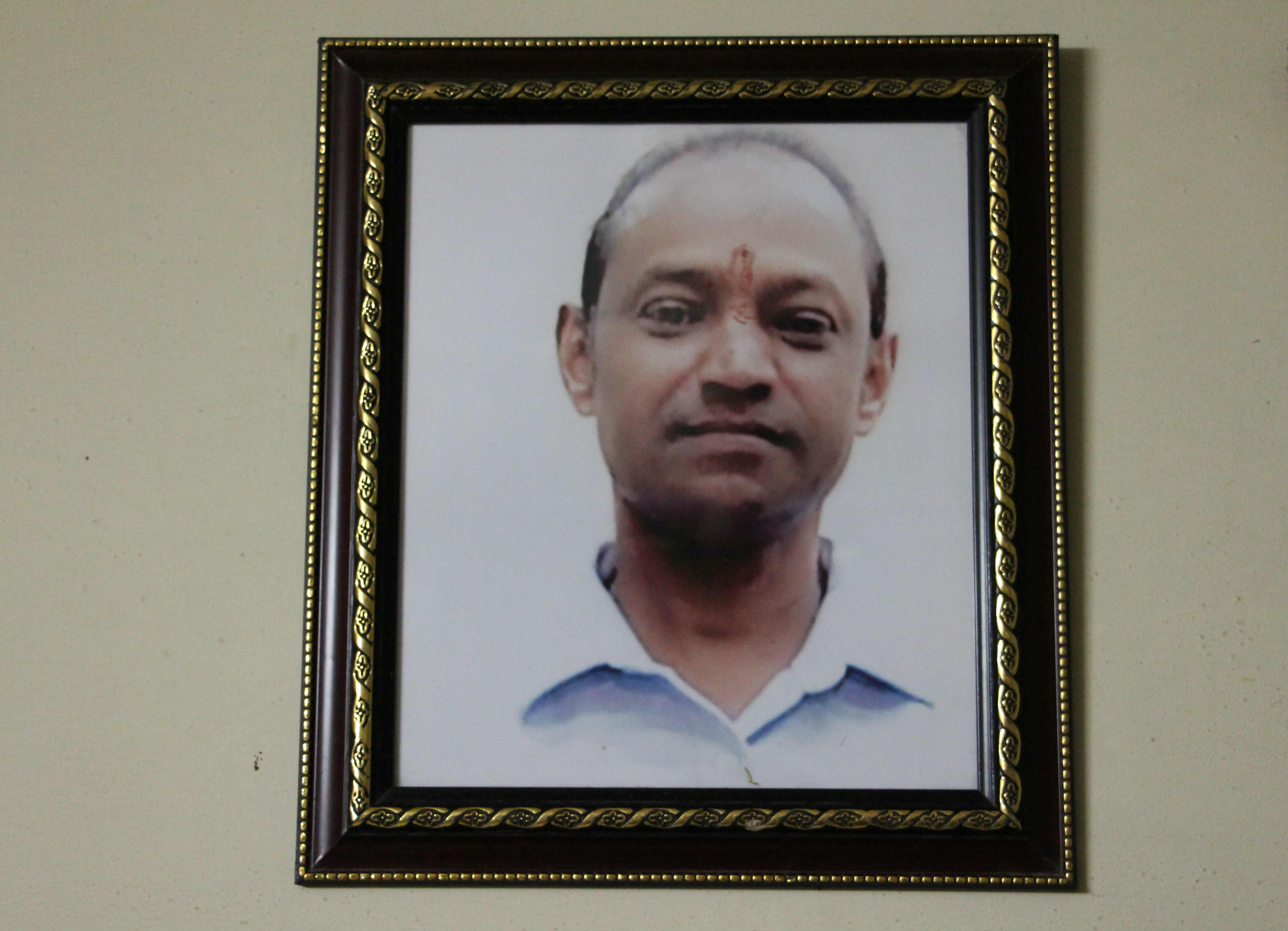 A portrait of Ravinder Kanojia hangs in his home in Ghazipur, Delhi. Photo credit: Aabid Shafi