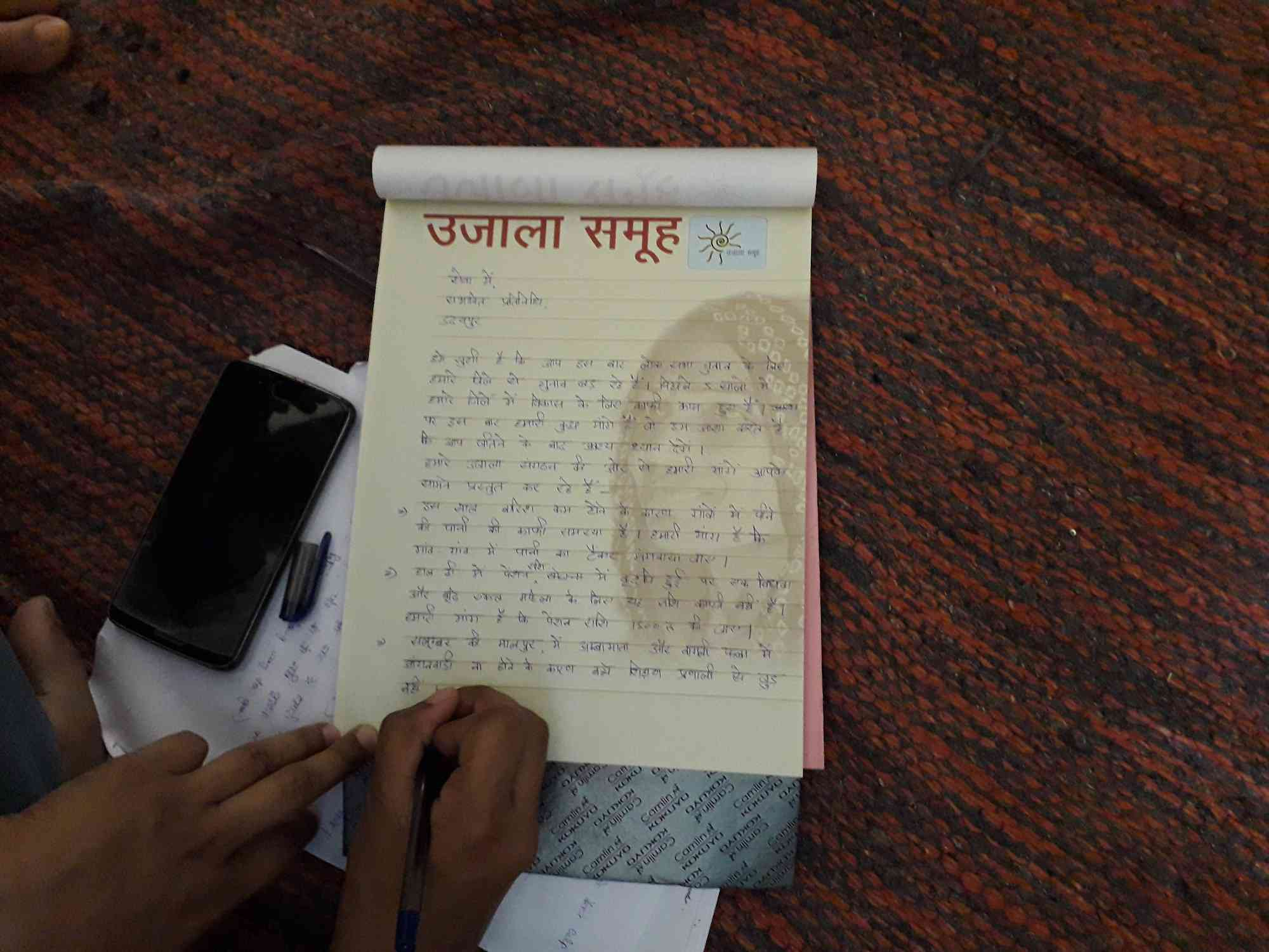 A social worker from Aajeevika Bureau helps women from the Ujala collective write a charter of demands from local poll candidates.