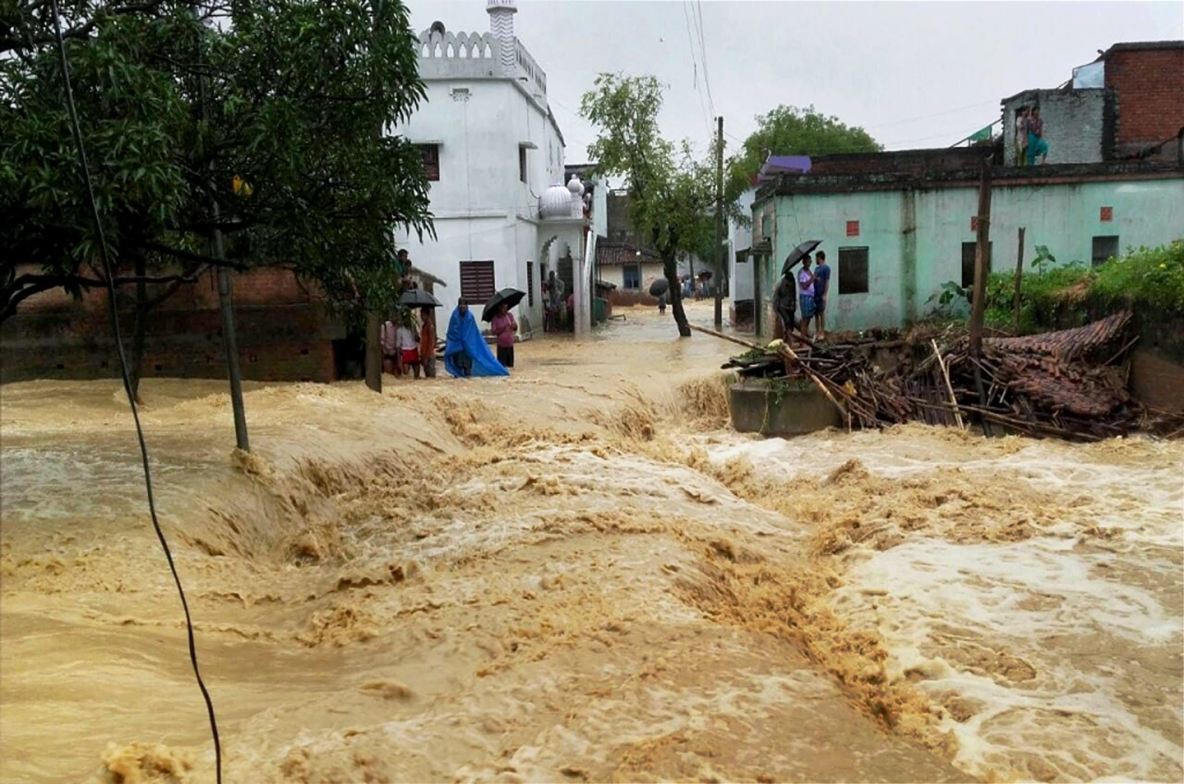 Floodwaters gush through a street in West Champaran, Bihar. (Credit: PTI)