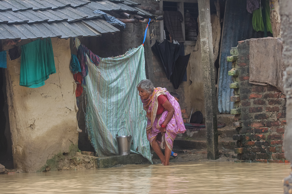 A woman walks in front of her flooded home. Photo credit: Munna Saraff