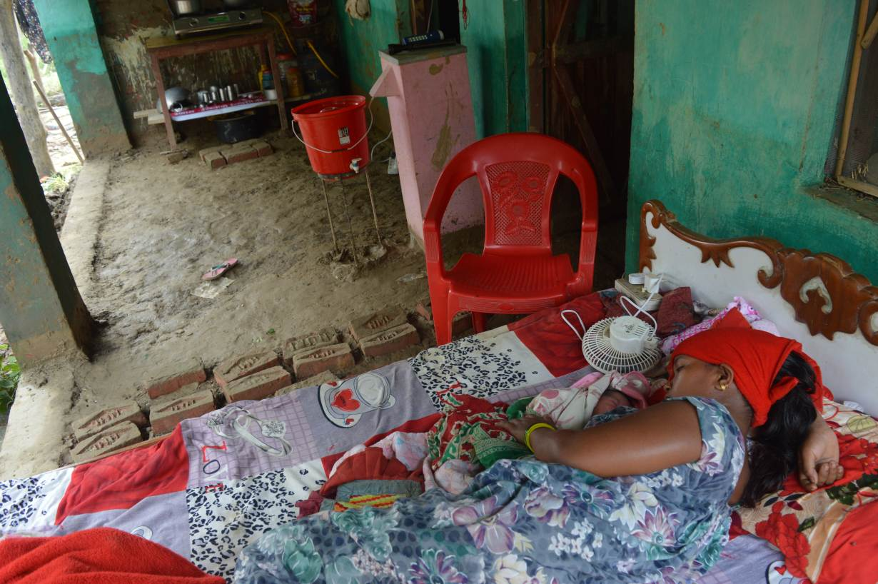 Shreejana Pariyar lies with her newborn on a bed on her front porch in Taduwa, Nepal, August 16. Photo credit: Arun Karki/Thomson Reuters Foundation