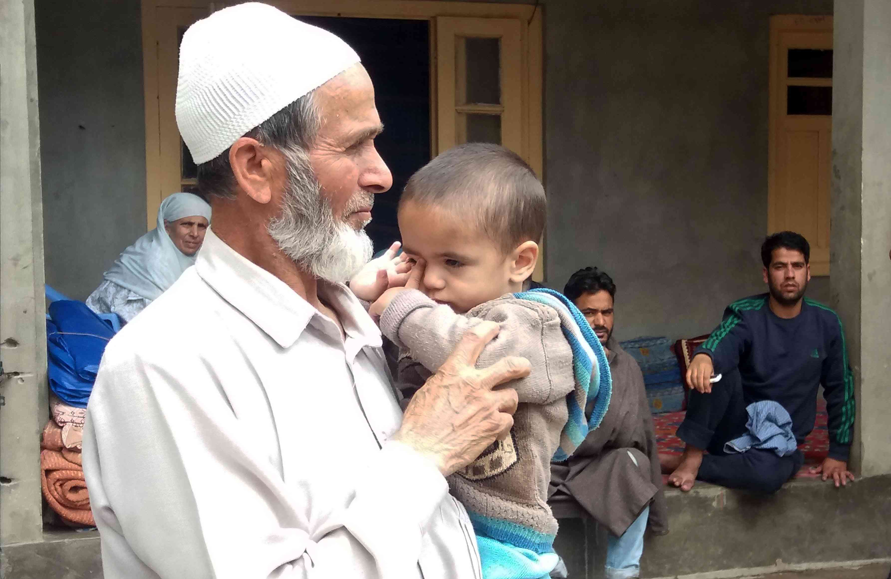 Shabir Ahmed Mangoo left behind a 15-month-old child in 2016. His father holds his grandson days after the raid in Shar-i-Shali
